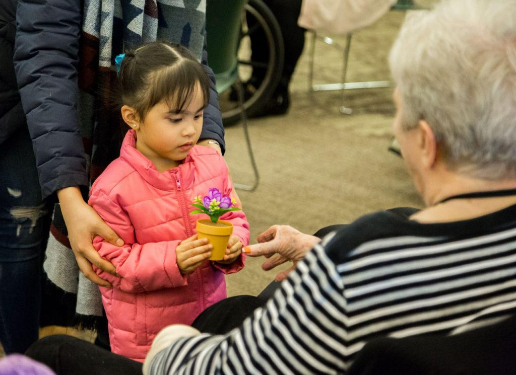 young girl presenting a gift to elderly woman.