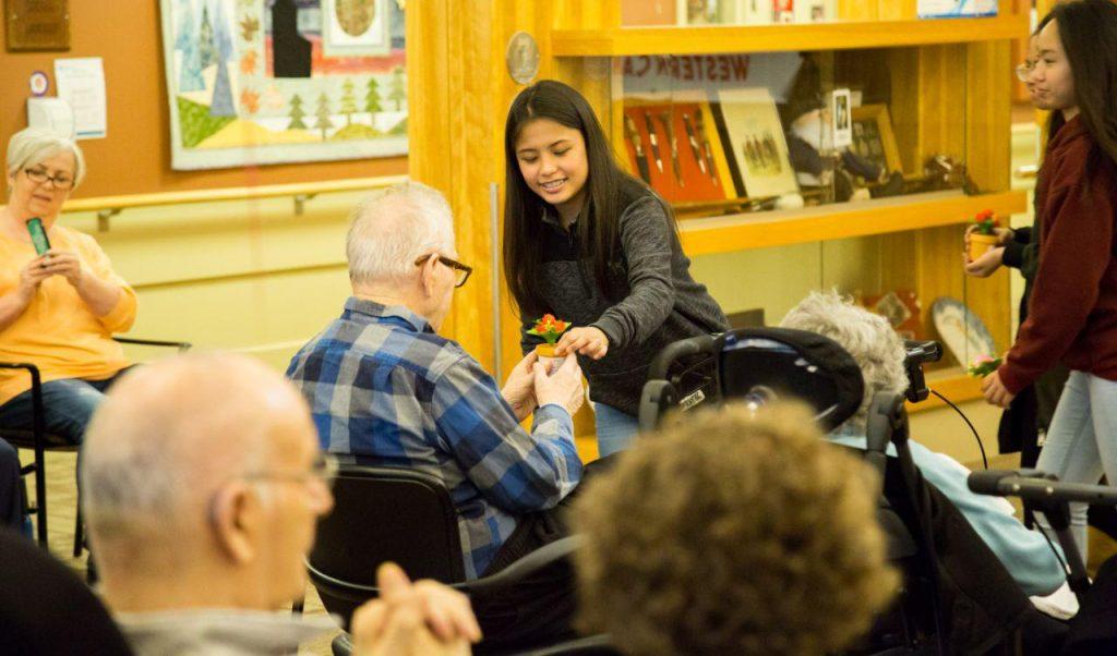 girl handing a gift to elderly man.