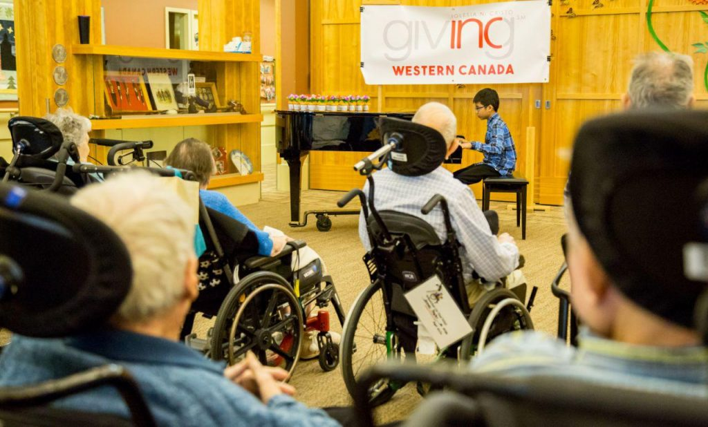 young man playing piano for elderly residents